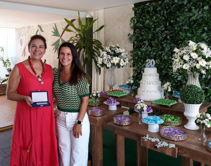 A conselheira do Grupo Athia e idealizadora do CCI, Christiane Athia, recebe placa comemorativa de Nina Villas Boas, coordenadora dos Planos Athia