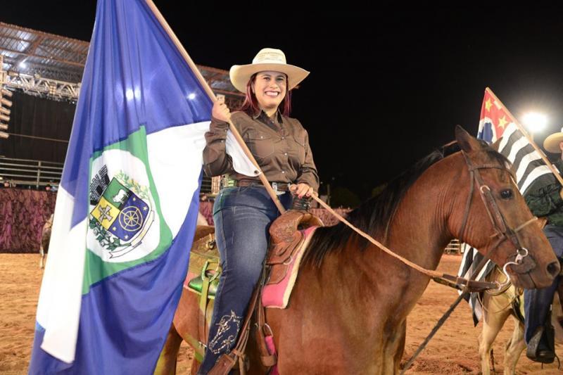Com a bandeira do município, prefeita de Sandovalina Amanda Lima de Oliveira Fetter faz a abertura do Rodeio Festival