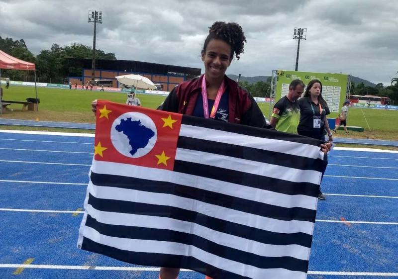 Organização JEJ - Com a bandeira de PP, Allana sorri no pódio por sua medalha de prata pela seleção paulista