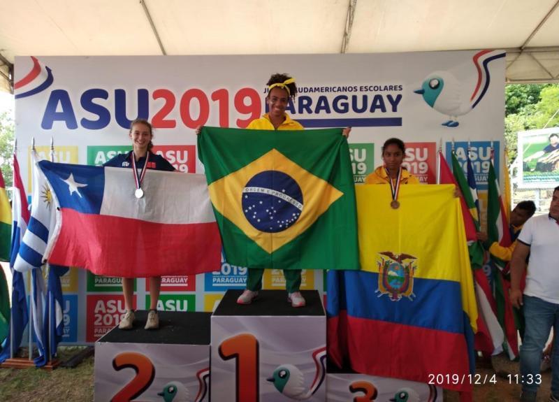 Divulgação - Allana no pódio mais alto, ladeada pelas companheiras de competição chilena e equatoriana