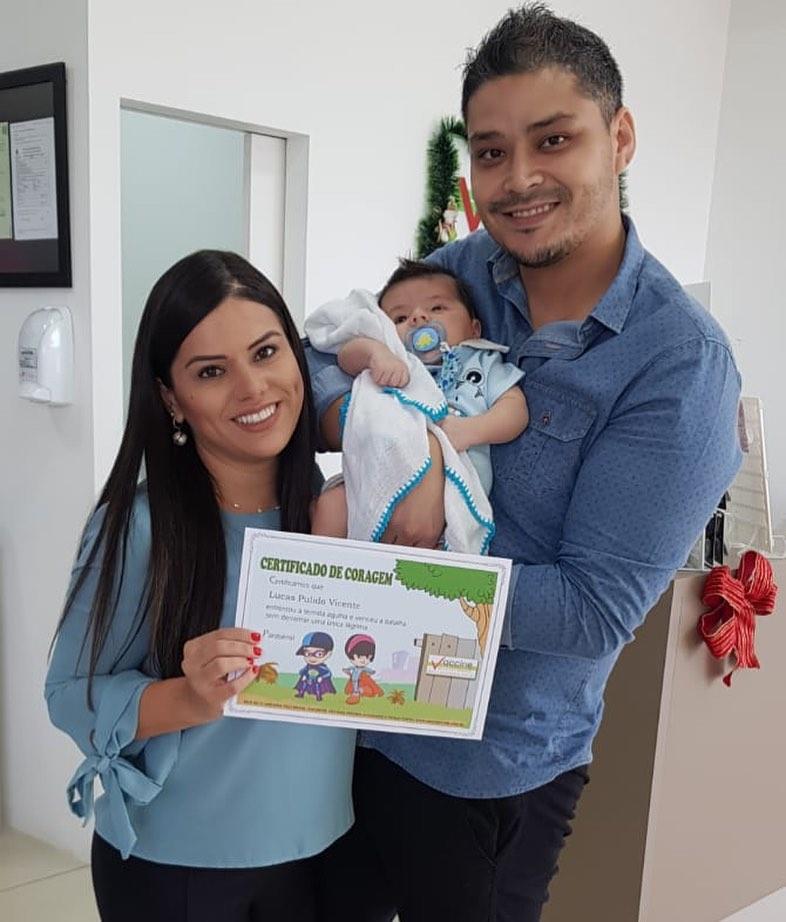 Pequeno Lucas, com os pais Ivan e Aline Pulido, recebe o certificado coragem de vacinação da Vaccine Care
