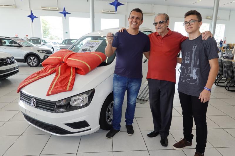 Adriano Nunes, ganhador do Gol sorteado sábado na Liane Veículos, na foto com seu filho Guilherme Nunes, 17 anos, e o empresário Laudério Bortigeli
