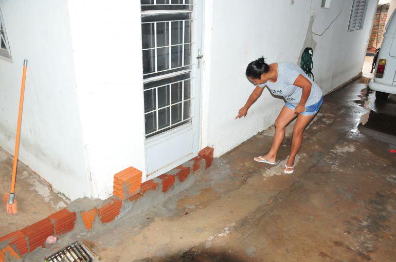 Arquivo - Paula aponta para as marcas do nível que a água atingiu na chuva do último fim de semana