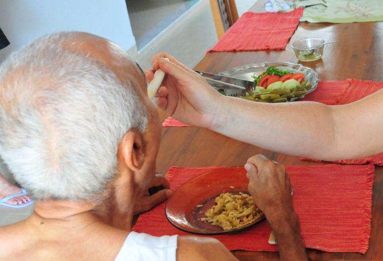 """Marcio Oliveira - Cilene ajuda o pai, que sofre de Alzheimer, a fazer as refeições: """"Ele não consegue mais comer sozinho"""""""
